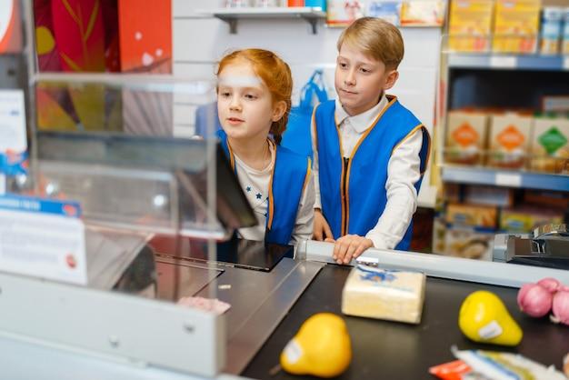 Meisje en jongen in uniform bij de kassa