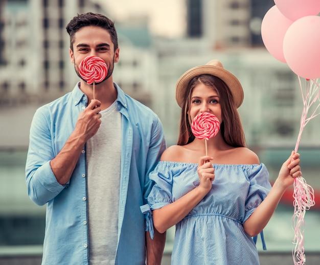 Meisje en jongen met ballen in hun handen en snoep op hun gezicht. man met meisje met lollipop chups op lippen in het midden van de straat.