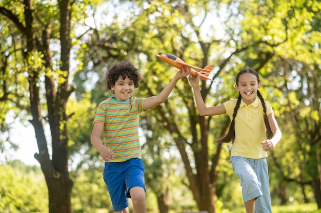 Meisje en jongen met speelgoedvliegtuig dat in het park loopt