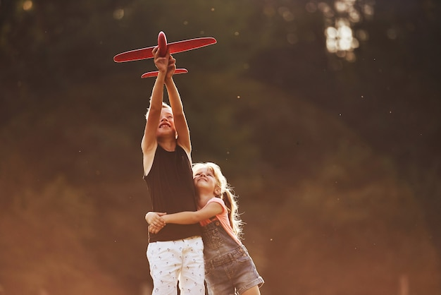 Meisje en jongen plezier buitenshuis met rood speelgoed vliegtuig in handen.