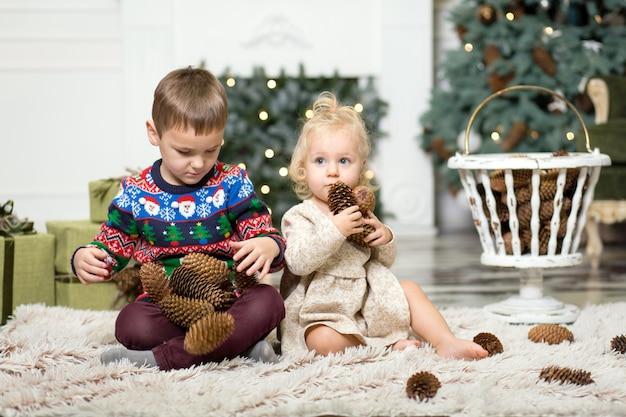 Meisje en jongen spelen op de vloer met kegels om de kerstboom te versieren.