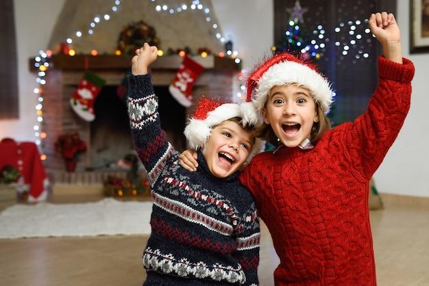 Meisje en jongen vieren met een opgeheven wapen