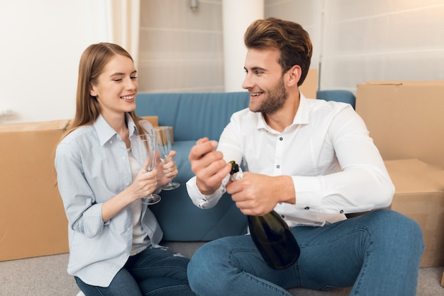 Meisje en jongen vieren verhuizen naar appartement met champagne.