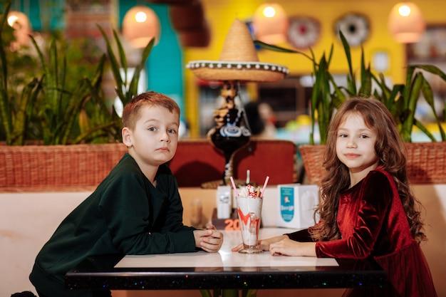 Meisje en jongen zitten aan een tafel in een café met een milkshake