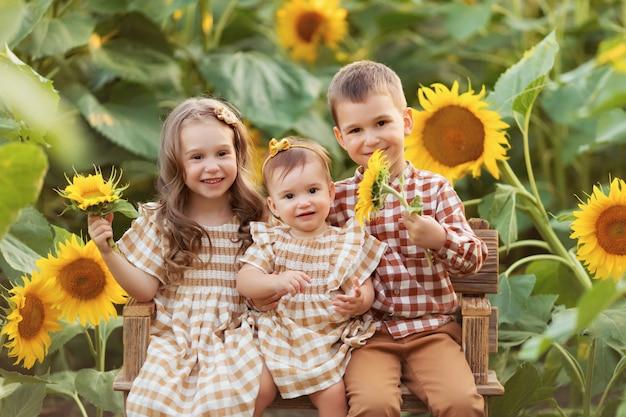 Meisje en jongen zitten op een bankje en hebben plezier tussen bloeiende zonnebloemen bij zonsondergang