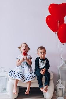 Meisje en jongen zittend op een witte stoel in de buurt van hartvormige ballonnen. meisje dat een rode lolly likt. valentijnsdag concept.