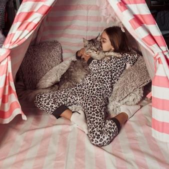 Meisje en kat in het afstandsschot van de tent