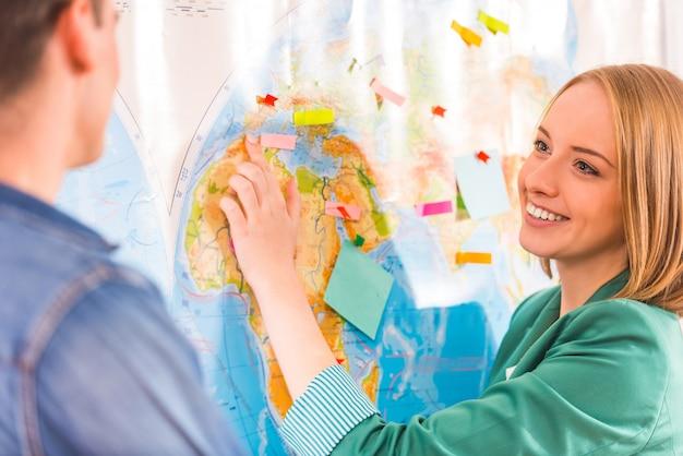 Meisje en man kijken elkaar op een kaart aan.