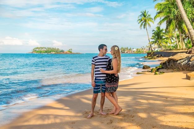 Meisje en man op het strand aan de oceaan.