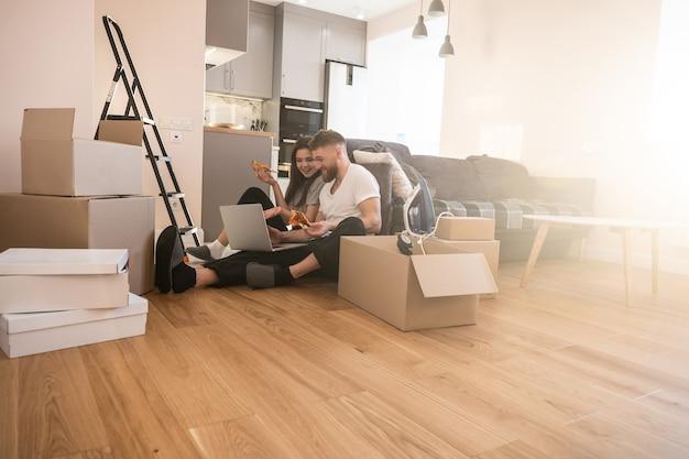 Meisje en man pizza eten en laptop thuis gebruiken. jonge lachende europese paar. kartonnen dozen met dingen. concept van verhuizen in nieuwe flat. idee van jong gezin. interieur van zonnig studio appartement