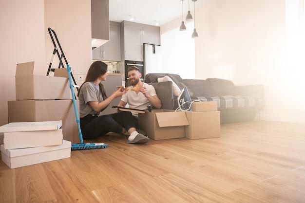Meisje en man zitten op de vloer en eten pizza thuis. jonge lachende europese paar. kartonnen dozen met dingen. concept van verhuizen in nieuwe flat. idee van jong gezin. interieur van zonnig studio appartement