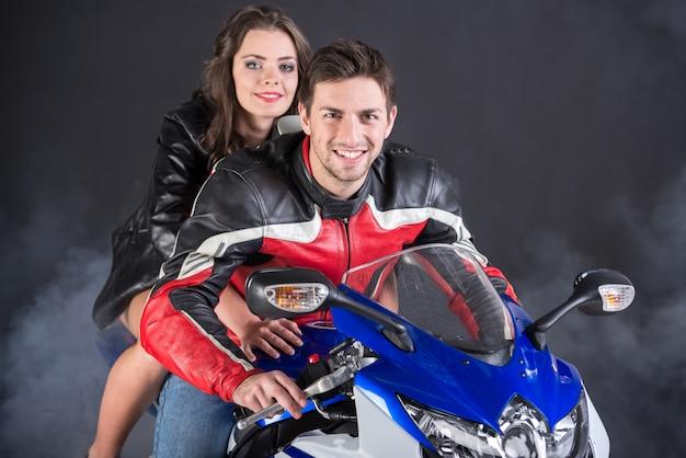 Meisje en man zitten op een motorfiets en glimlachen.