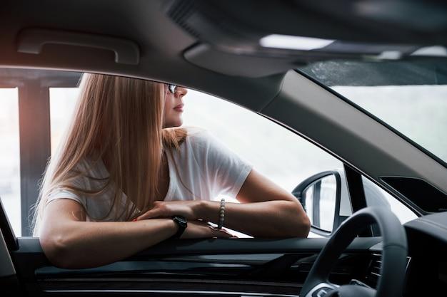 Meisje en moderne auto in de salon. overdag binnenshuis. een nieuw voertuig kopen