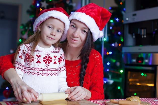 Meisje en moeder de peperkoekkoekjes van kerstmis bakken
