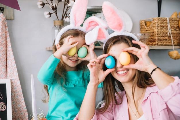 Meisje en moeder die kleurrijke paaseieren houden bij ogen
