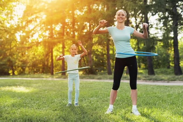 Meisje en moeder in het park verdraaien de gymnastiek hoepels.