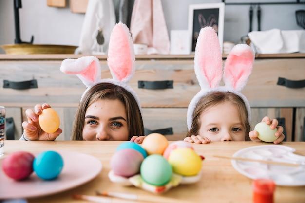 Meisje en moeder in konijntjesoren die achter lijst met gekleurde eieren verbergen