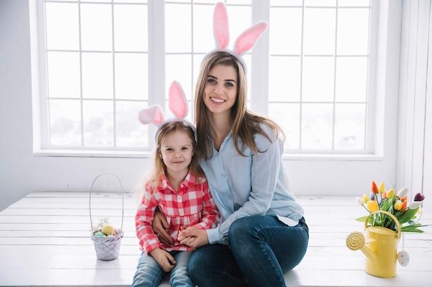 Meisje en moeder in konijntjesoren die dichtbij mand met gekleurde eieren zitten