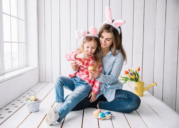 Meisje en moeder in konijntjesoren die eieren voor pasen schilderen