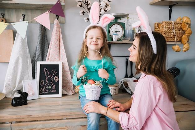 Meisje en moeder in konijntjesoren die met mand van paaseieren zitten