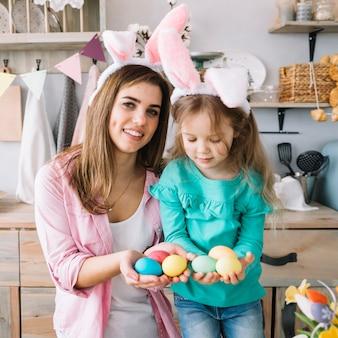 Meisje en moeder in konijntjesoren die paaseieren in handen houden