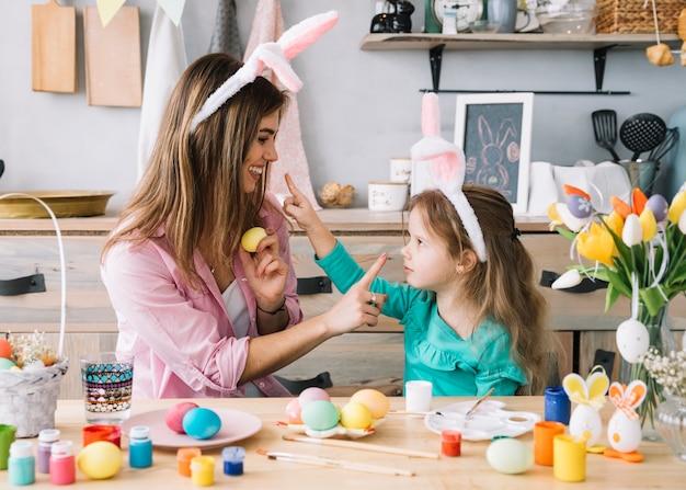 Meisje en moeder in konijntjesoren die pret hebben