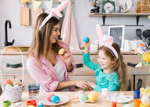 Meisje en moeder in konijntjesoren die pret met paaseieren hebben