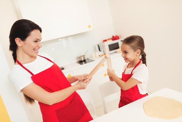 Meisje en moeder lachen en rollen met deegrollen.
