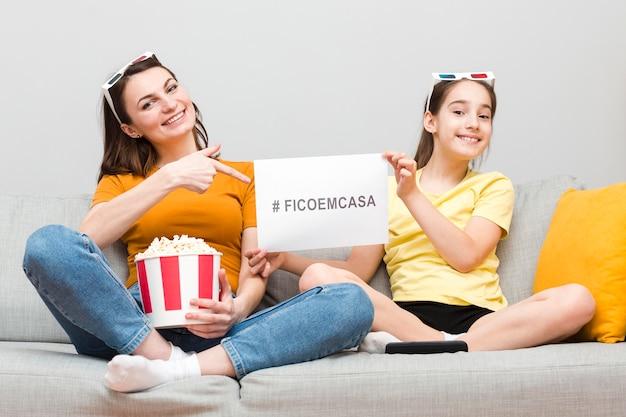 Meisje en moeder op bank met popcorn