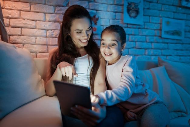Meisje en moeder zitten thuis en kijken 's nachts naar iets.