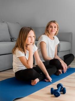 Meisje en moeder zittend op de mat