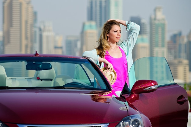 Meisje en rode auto. schoonheid en auto's.