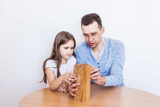 Meisje en vader spelen thuis een spel, kosten een toren van blokken, blokjes, jenga, puzzel voor hersenontwikkeling, mentale intelligentie