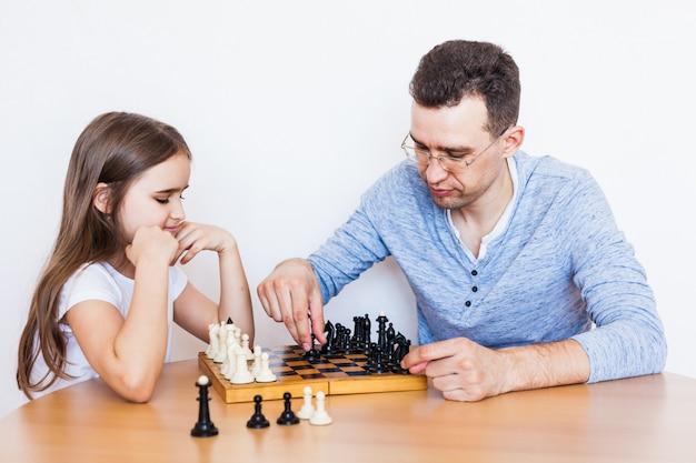 Meisje en vader spelen thuis een spelletje, schaken, puzzelen voor hersenontwikkeling, mentale intelligentie