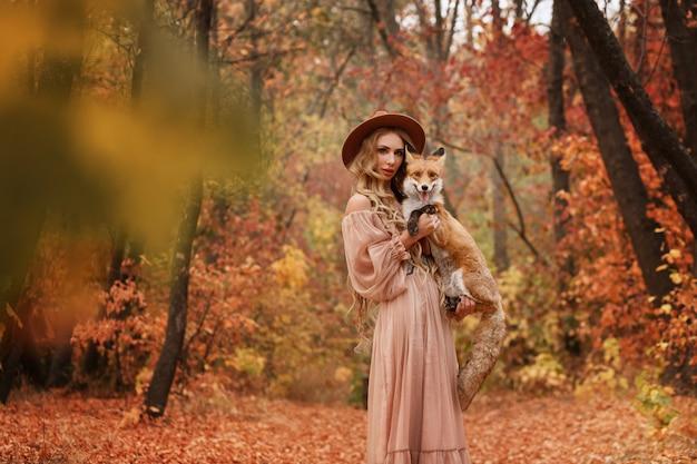 Meisje en vos in het bos in de herfst