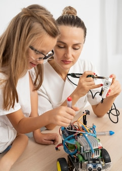 Meisje en vrouwelijke leraar doen wetenschappelijke experimenten met robotachtige auto