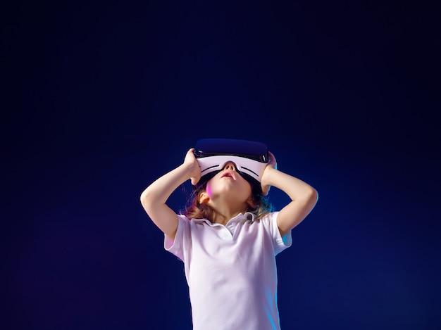 Meisje ervaart vr-headsetspel. kind gebruikt een gaminggadget voor virtual reality.