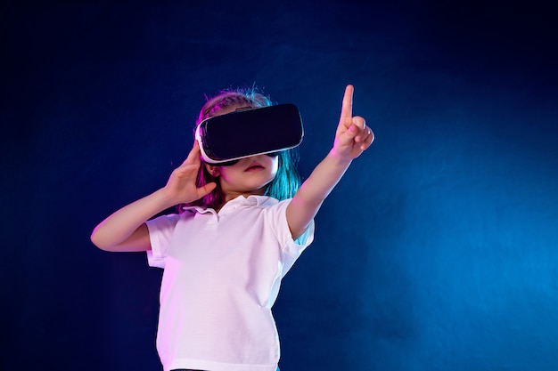 Meisje ervaart vr-headsetspel. kind wijzende vinger tijdens het gebruik van een gaminggadget voor virtual reality.