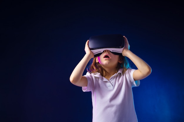 Meisje ervaart vr-headsetspel. verraste emoties op haar gezicht. kind met een gaminggadget voor virtual reality.