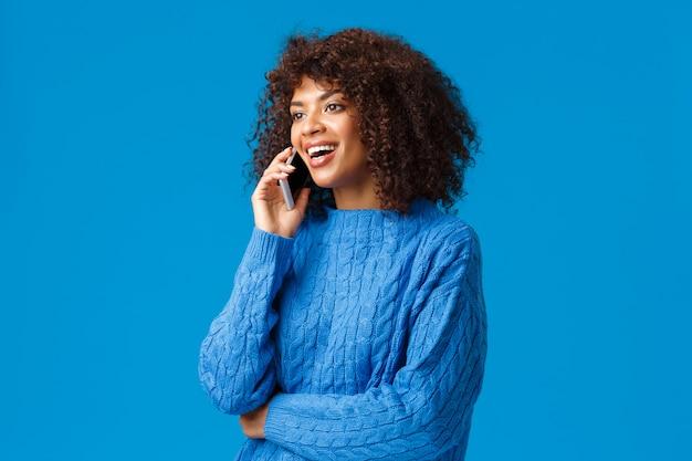 Meisje feliciteert familie met fijne feestdagen, wenst goed nieuwjaar als praten over de telefoon vanuit het buitenland, houdt smartphone aan het spreken, belt vriend, kijkt naar links en lacht, blauwe muur