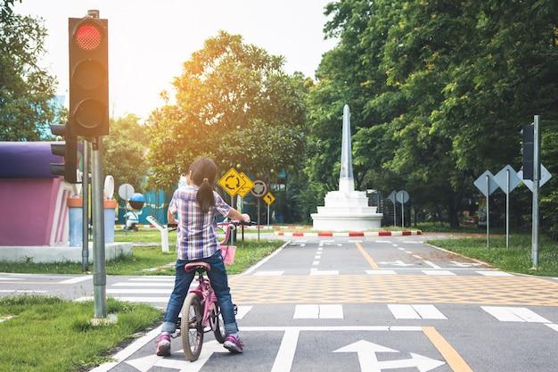 Meisje fietst in het park, fiets stopt bij verkeerslichten