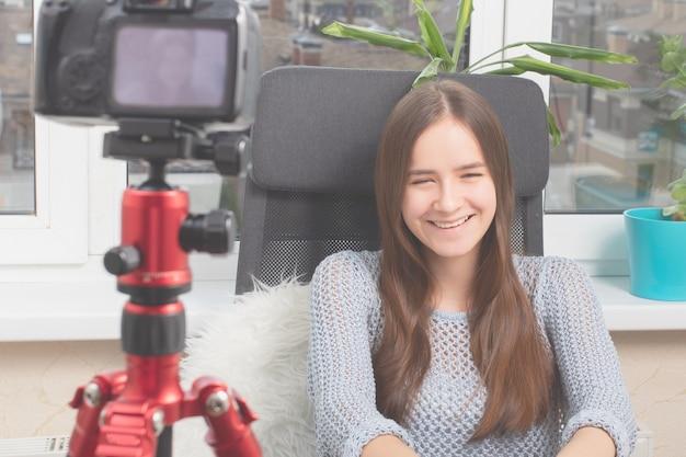 Meisje filmt zichzelf thuis voor de camera, glimlacht, lacht