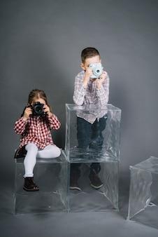 Meisje fotograferen met camera en jongen fotograferen met vintage instant camera