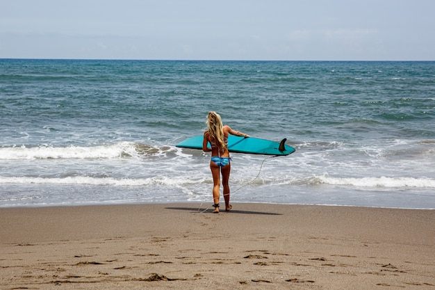 Meisje gaat het water in om te surfen.
