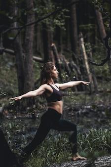 Meisje gaat sporten in het bos. in de lotushouding. oefeningen, gymnastiek, ontspanning. gezonde levensstijl.