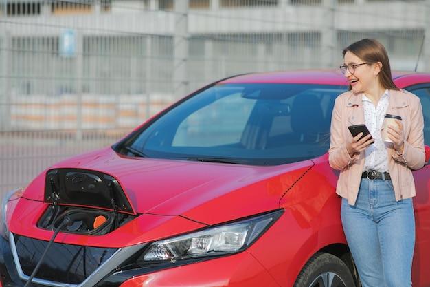 Meisje gebruikt koffiedrank tijdens het gebruik van een smartphone en wachtende voeding sluit aan op elektrische voertuigen om de batterij in de auto op te laden