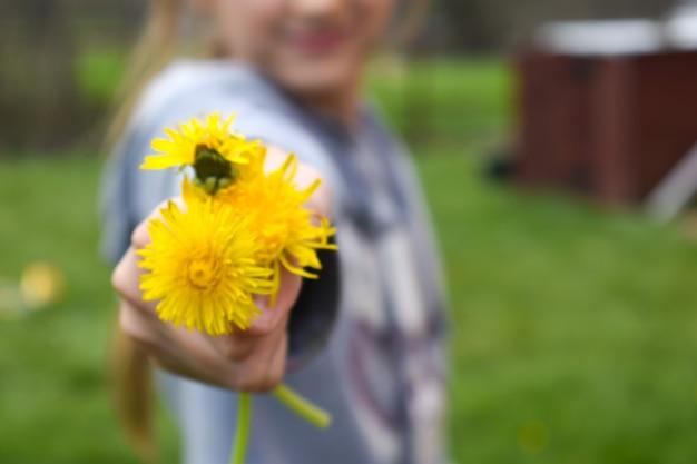 Meisje geeft een boeket gele paardebloemen, bloemgift