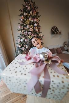 Meisje geeft een cadeau op de achtergrond van een kerstboom