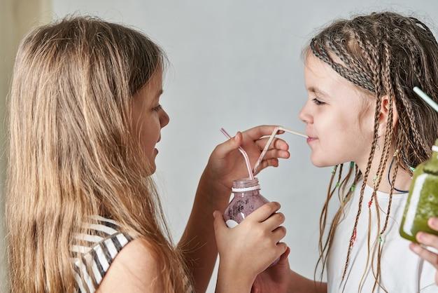 Meisje geeft haar bessensmoothie naar smaak door een rietje uit een doorzichtige fles
