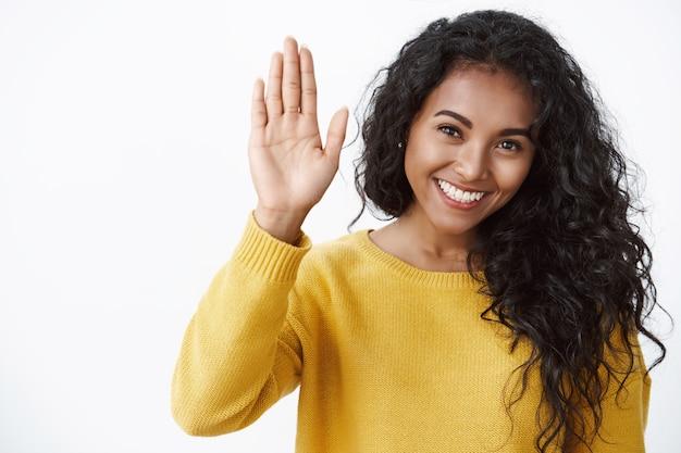 Meisje geeft high five, blij met productief teamwerk. vrolijke vrouw met krullend haar steekt hand op om vriend te feliciteren met goed gedaan werk, glimlachend ondersteunende, witte muur